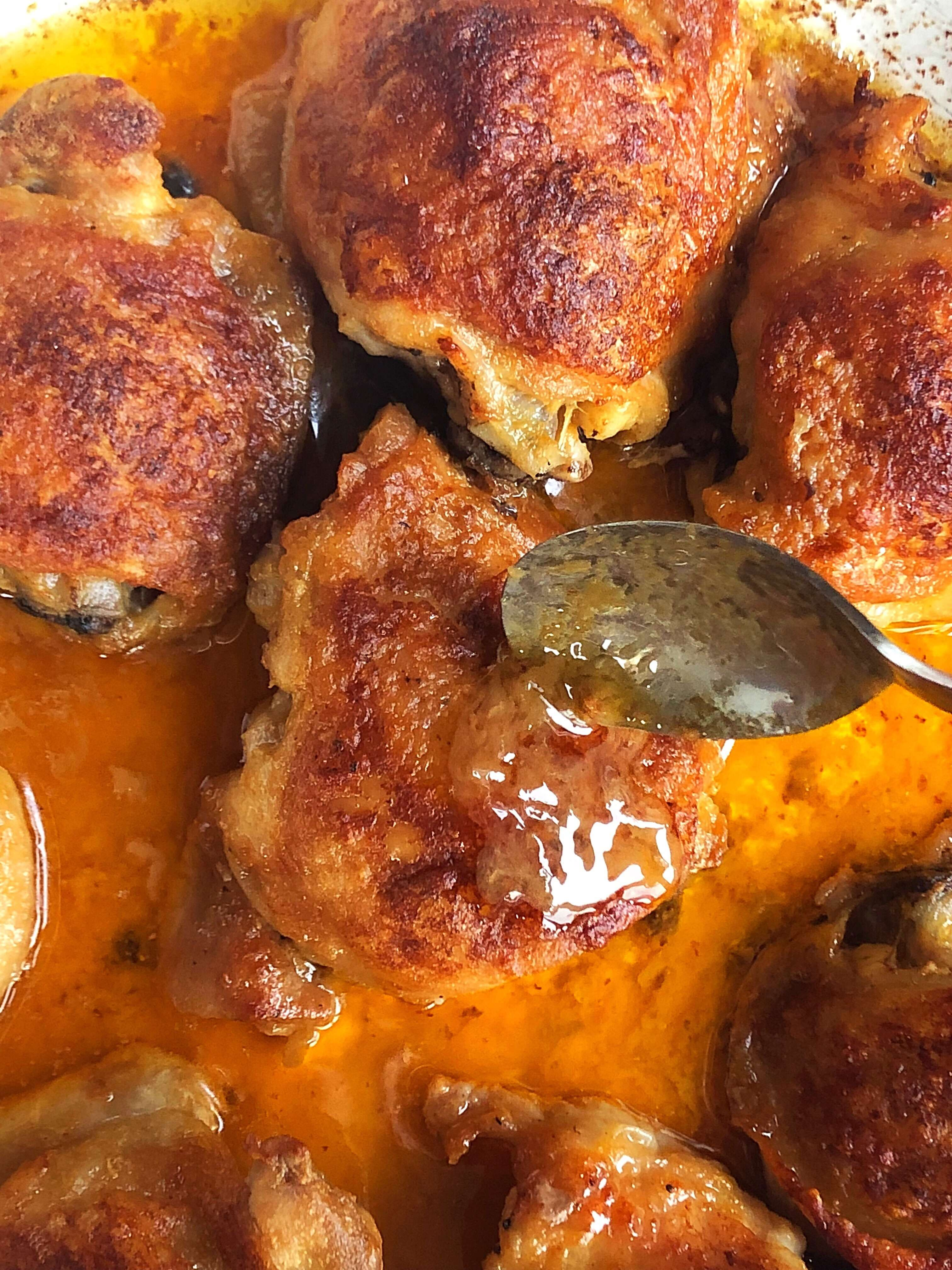 Basting the baked chicken thighs
