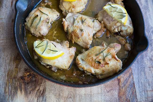 Oven Baked Chicken Thighs topped with Lemon and Rosemary in an Oven Safe Skillet